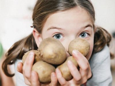 Девочка с картофелем в руках