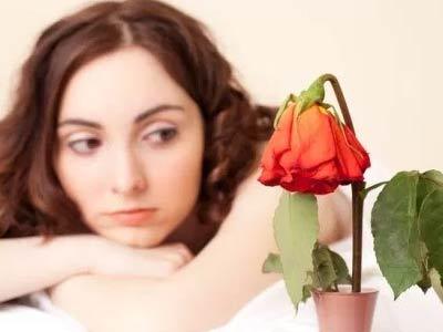 девушка смотрит на увядающий цветок